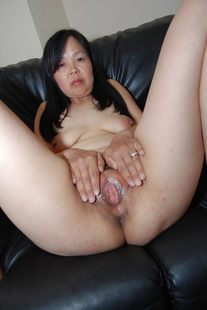 Mature Asian female undresses and introduces her hairy beaver
