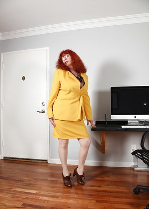 Sexy, mature secretary poses in front of camera and undresses