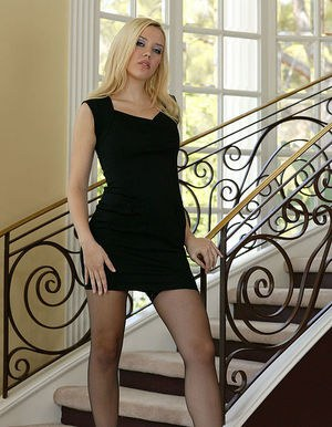 Impressive blonde in black, lacy stockings lies on staircase