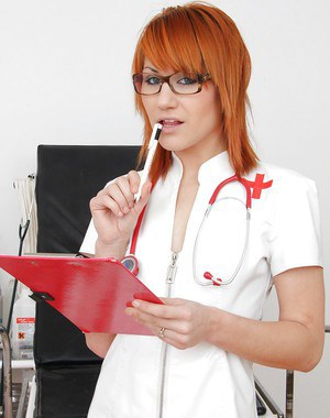 Redhead nurse in glasses and stockings playing with a speculum