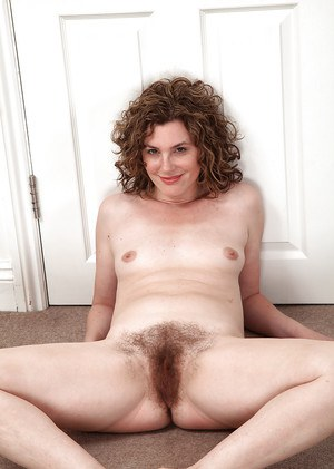 Smiley mature gal with shaggy bush getting nude and spreading her legs