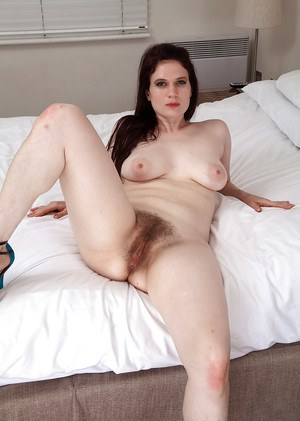 Sassy mature lady getting naked and exposing her hairy gash in close up