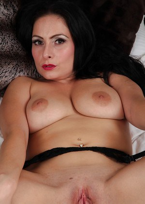 Raven-haired mature vixen getting nude and exposing her pink pierced cunt