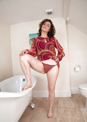 Naughty MILF undressing and spreading her unshaven cunt in the bathroom