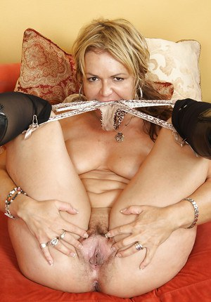 Sassy MILF in nylons and high heeled boots undressing and spreading her cunt
