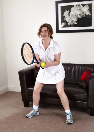 Playful mature tennis player takes off her panties and exposes her bushy cunt