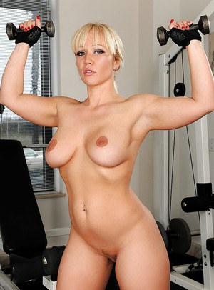Playful blonde bodybuilder uncovering her curvy body in the gym