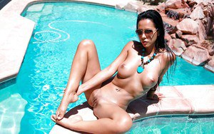 Immensely sexy brunette babe in glasses tans over the swimming pool