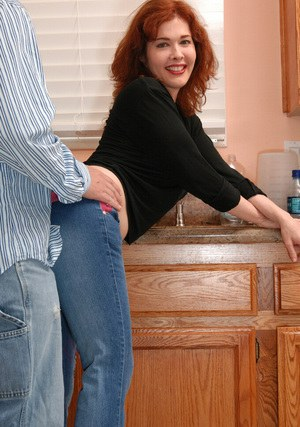 Big busted redhead lady gives a sensual blowjob in the kitchen