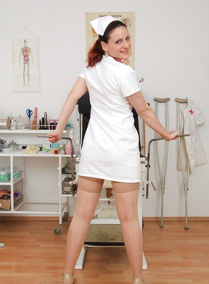 Sassy mature gyno nurse taking off her thongs and playing with a speculum
