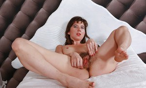 Lusty MILF in lingerie and nylons revealing her feet and bushy cunt