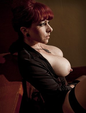 Sassy redhead MILF in sexy girdle exposing her jugs and teasing her twat