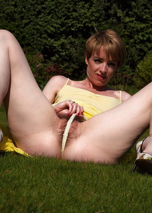 Mature amateur babe Maria lies half-naked on a green field alone