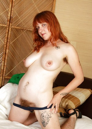 Redhead mature unshaven lassie getting rid of her clothes