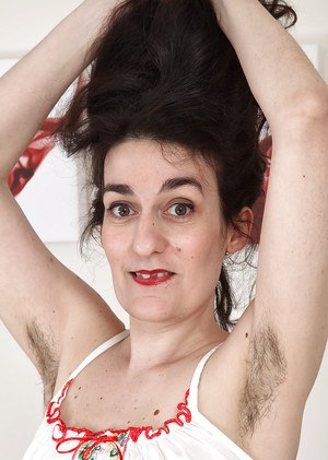 Ugly mature woman with hairy armpits and pussy strips on camera.