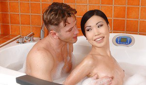 Wet Asian girl Nicoline presents a blowjob in the bath for two guys