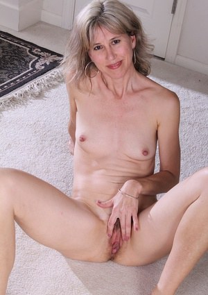 Olive Jones shows her tiny tits and hairy mature pussy while undressing