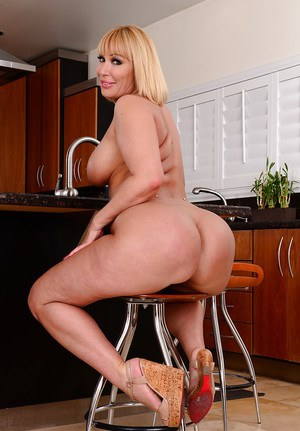 Huge tit blonde Mellanie unressing in the kitchen and posing