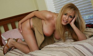 Big tit blonde cougar milf Nicole loves to undress on the bed