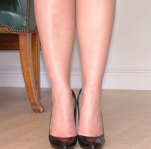 Jackie is revealing her slim legs in tight white skirt and high heels