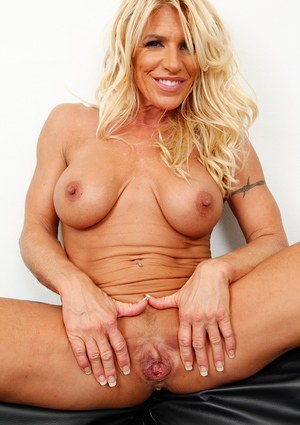 Mature blonde with big tits Gina West showing ass in pink panties