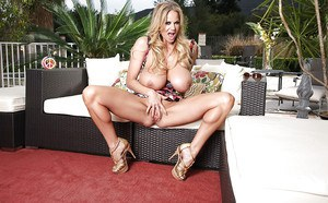 Kelly Madison is masturbating her shaved pussy while in high heels