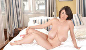 Brunette cutie Luna Amor is masturbating her shaved pussy on a bed