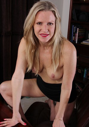 Clothed mature beauty Tabitha Green demonstrates her legs in close up