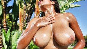 Oiled big tits of an ebony babe Andrea Marquez shown in a bikini
