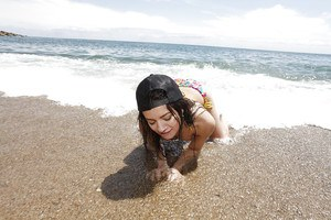 Tiny tits teen babe Alicia Poz reveals her Asian ass on the beach