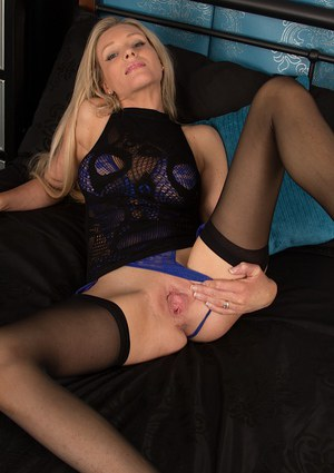 Mature chick Angel P. teases her tight pussy in black stockings