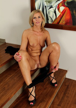 Blonde babe Carrie teases her milf pussy while posing on stairs