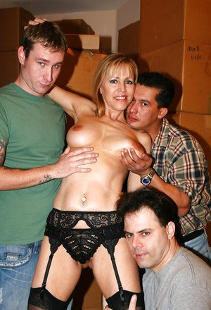 Mature slut Nicole Moore takes part in a gangbang action while in stockings