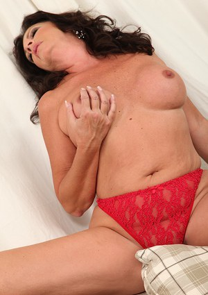 Mature babe with big tits Margo Sullivan undresses her red skirt