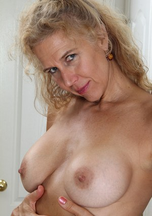 Mature blonde with big boobies Cally Jo shows her hairy pussy