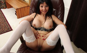 Office mature Marcy Darling is posing on the table and undressing