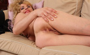 Awesome curly-haired blonde Liz is posing in the bedroom naked