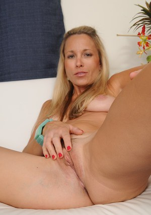 Gorgeous blonde with tanned tits is stroking her hard nipples