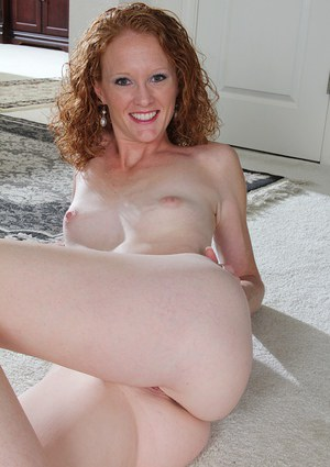 Skinny curly-haired mature woman Ande is posing on the stairs