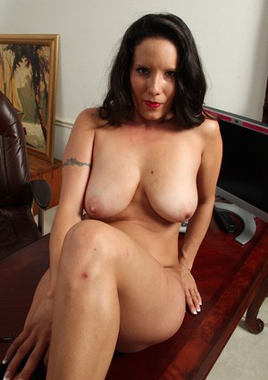 Mature brunette DeSire Delgoto pose in her glasses with naked boobies