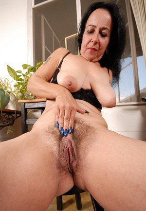 Spicy brunette mature Nina is licking her her saggy boobies!
