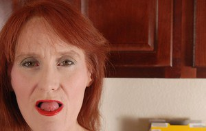 Redhead granny Debra is lying naked on the floor and masturbating