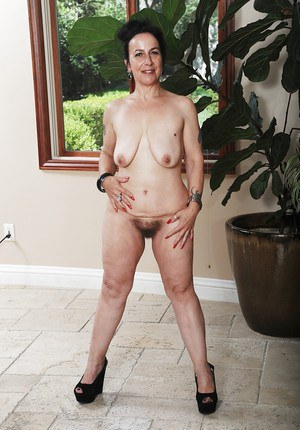 Tattooed mature chick Miss Nina Swiss is playing with her snatch