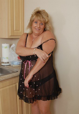 Fatty mature blonde Jenna undresses her black lingerie in the kitchen