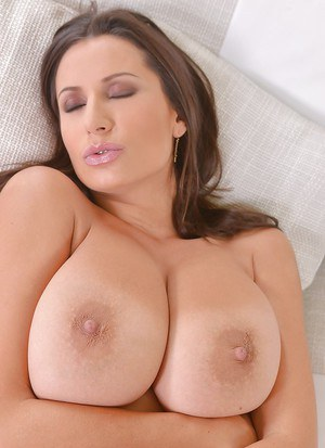 Busty milf Sensual Jane takes off her sexy pink blouse on sofa