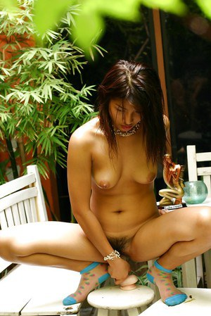 Thai chick is sucking this rubber dildo right in the garden!