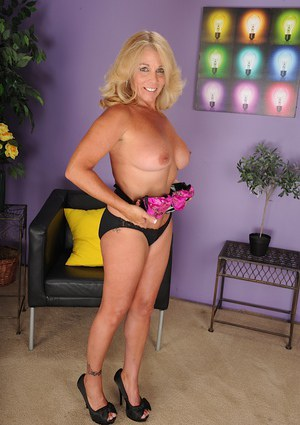 Mature blonde Crystal Taylor undressing and playing with puss