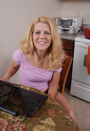 Sexy mature blonde Lori gets naked in the kitchen in close-up scene