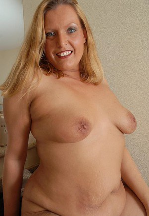 Chubby mature blonde Alexys is smiling while undressing on camera