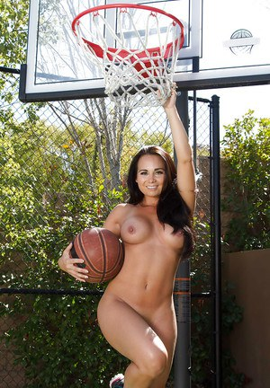 Sporty brunette Latina Holly West is playing basketball outdoors